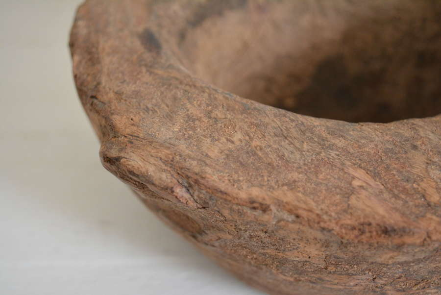 A RUSTIC WOODEN MORTAR OR BOWL